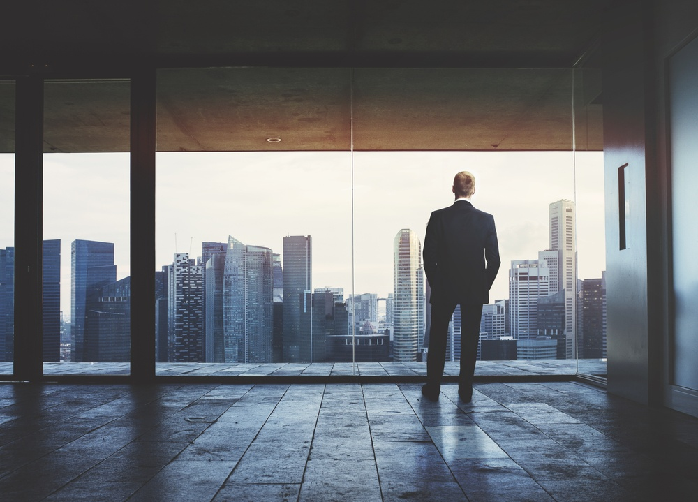 Man staring out floor to ceiling windows looking at a city skyline