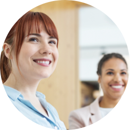 Circle photo of 2 women listening and smiling in a meeting