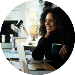 Circle photo of a woman holding a cup of coffee as she is listening to someone. She is sitting at a desk with her laptop open in front of her.