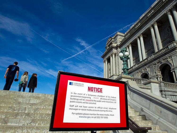 Close up of a sign disclaiming the closing of the library of congress in front of the library of congress