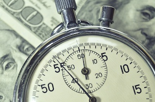 Close up of a pocket watch laying on top of one hundred dollar bills