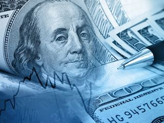 Close up of one hundred dollar bills and a pen on top