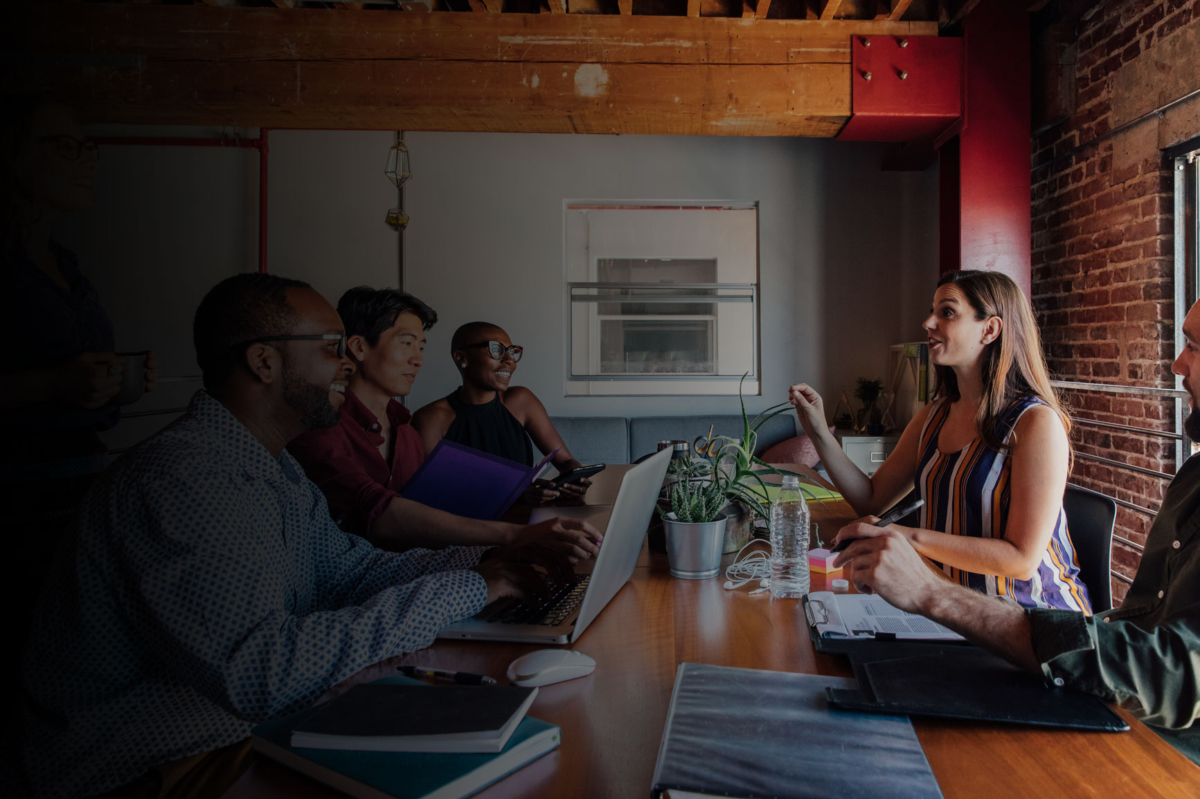 Photo of a woman leading a meeting at a communal table in a modern office