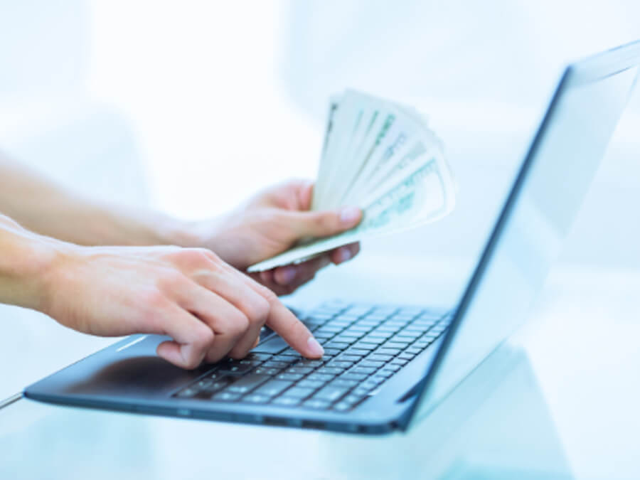 Close up of a person typing on a laptop with a handful of one hundred dollar bills in her other hand.