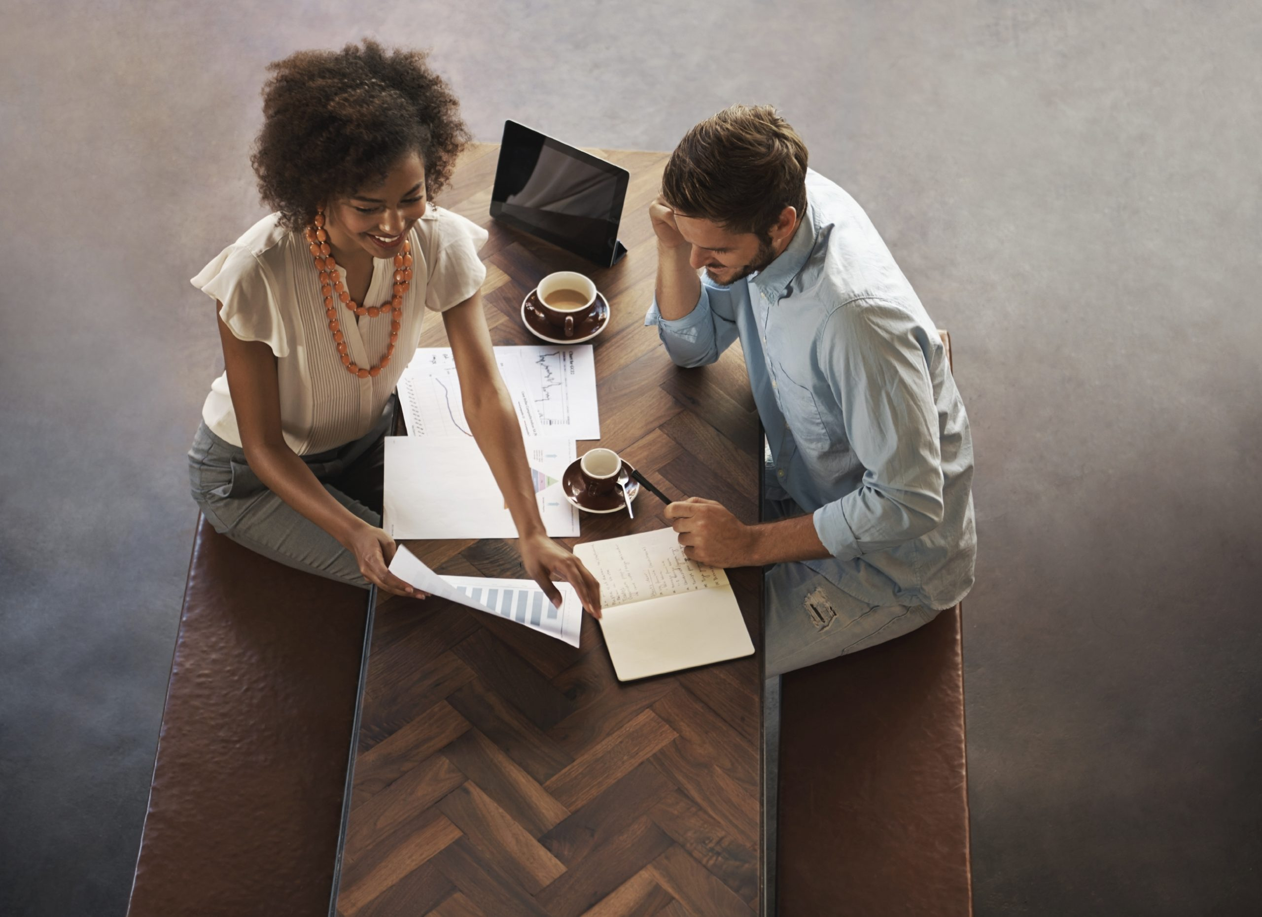 Shot of male and female having coffee while going over business ideas and proposals