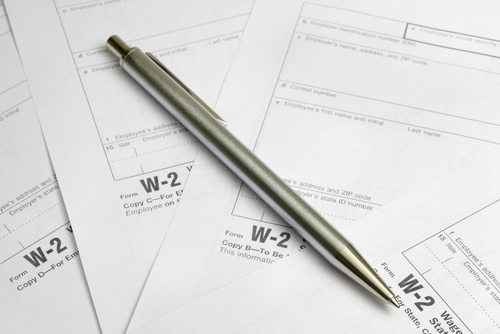 Close up of a pen lying on a lot of W-2 forms