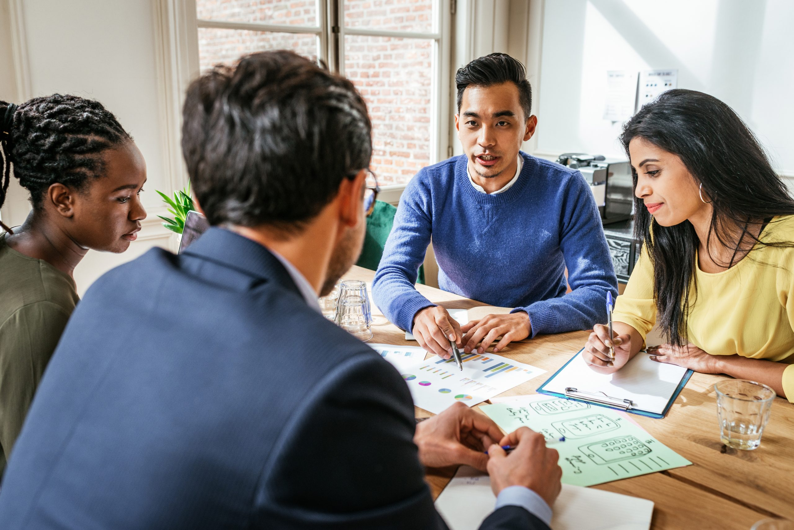 Multi ethnic group of Millennial investors planning new gainful activity
