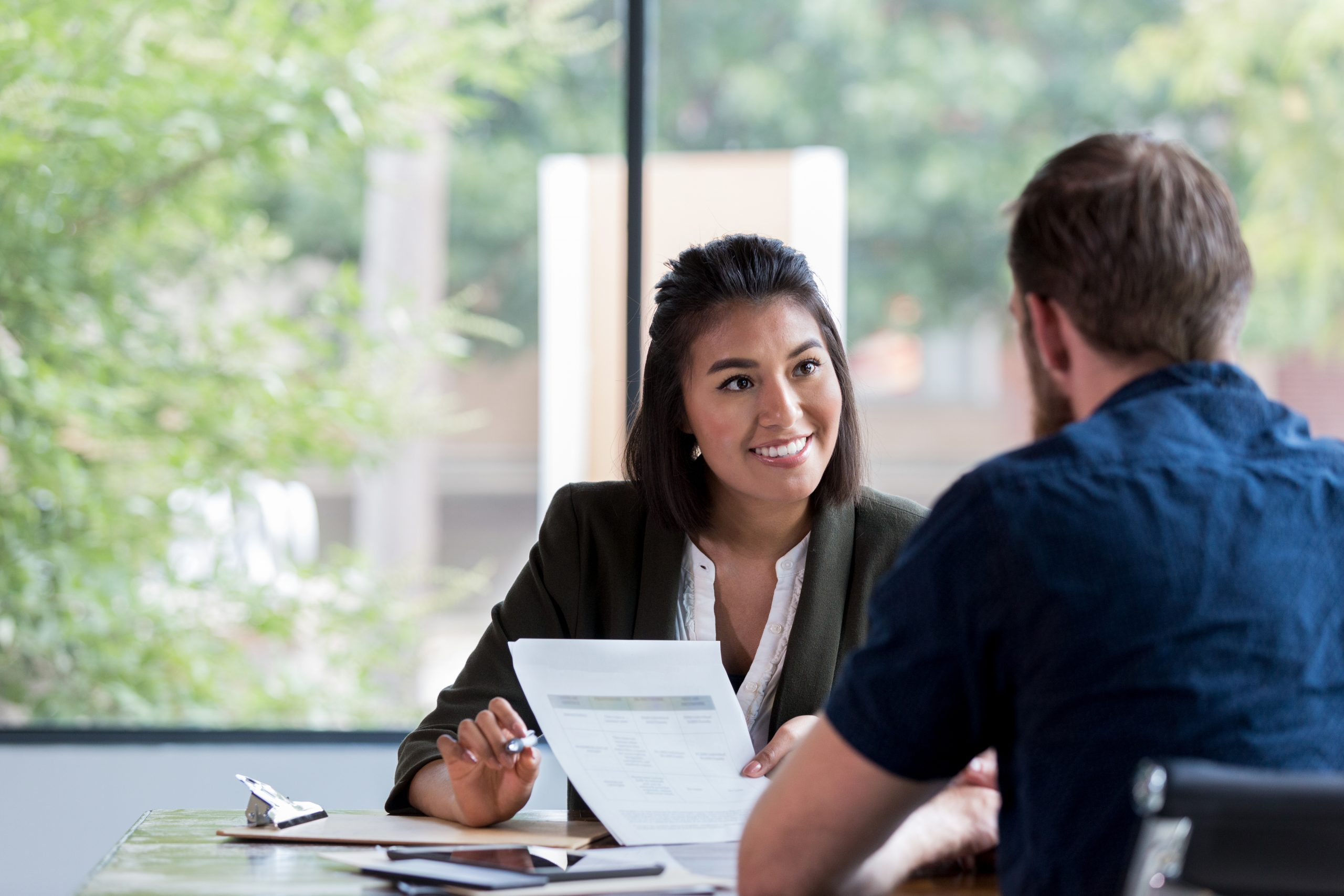 Hispanic businesswoman smiles while showing a document to a male associate.