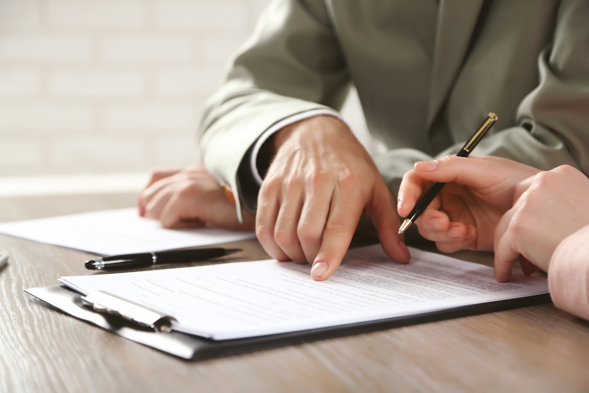 Close up of one employee signing contracts as the other points to details.