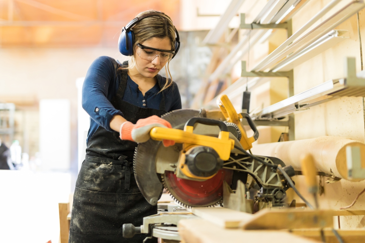 Woman with wood working protective gear on, sawing through a piece of wood.